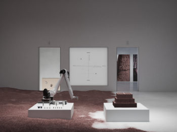 A gallery room with two low pedistals , one with a robotic arm and the other with ceramic bricks.